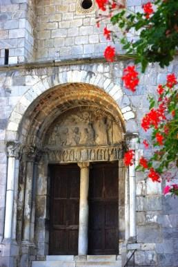 Le portail roman s'ouvre sous une profonde voussure à double archivolte retombant sur des piédroits à huit colonnes. La scène qui orne le tympan est une adoration des mages.