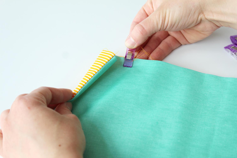 Untere kurze Kante 13 cm nach oben falten (Wachstuch liegt innen) und an den Seiten mit Stoffklammern fixieren.