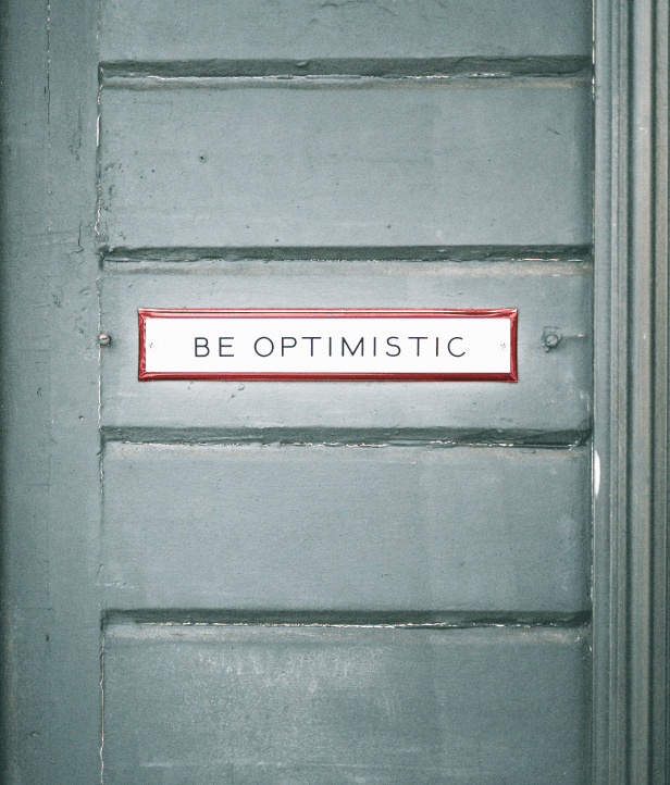 Sign on a door that reads 'Be optimistic'