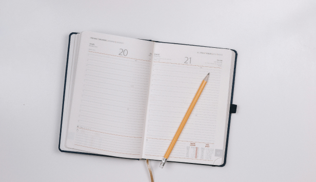 Open diary with pencil on plain white background