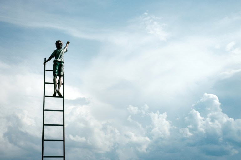 boy on a ladder reaching towards the clouds to signify self improvement