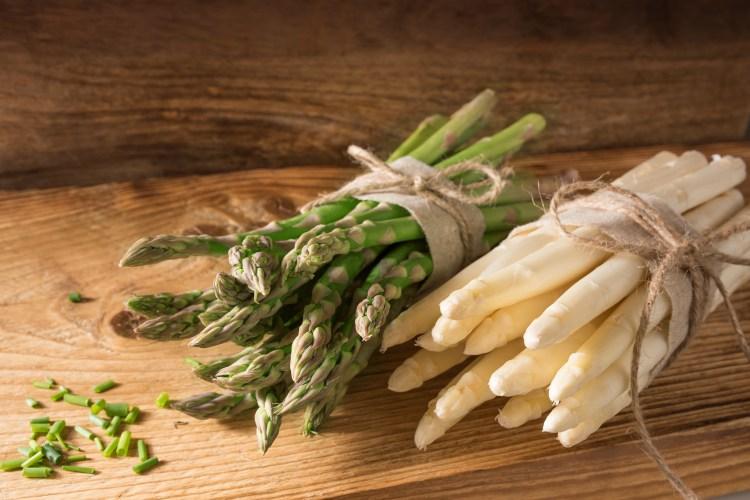 asparagi bianchi e verdi crudi su tavolo in legno