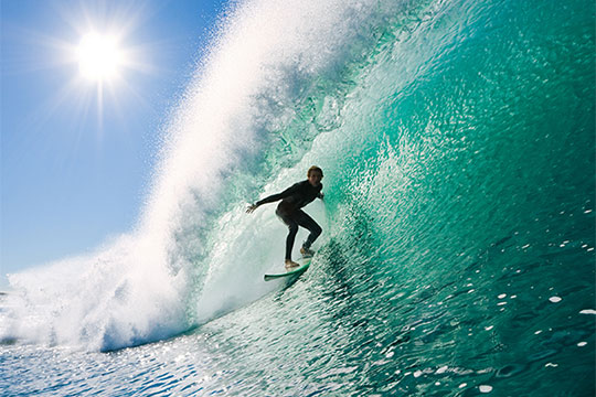 man surfing a big wave in the Maldives