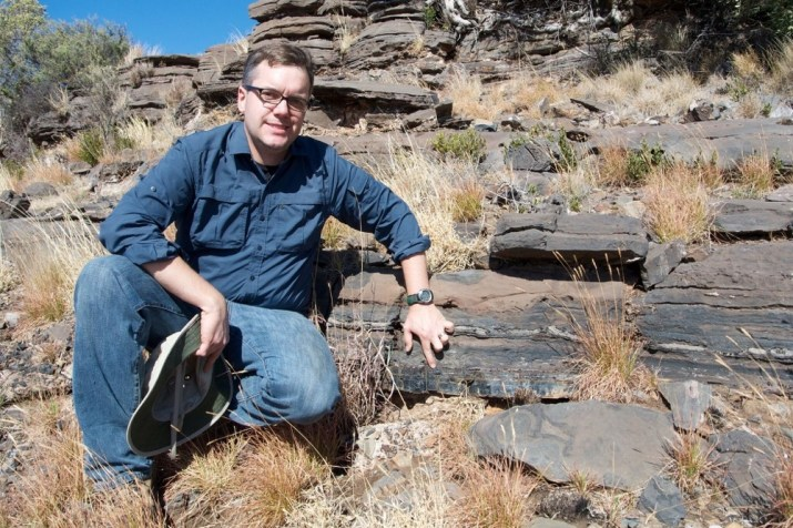 UC geologist, Andrew Czaja kneels beside a layer of ancient rock that contain fossilized bacteria.