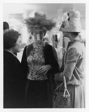 Three women try on hats in a clothing store.