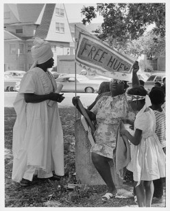 """Woman in caftan and children with """"Free Huey"""" banner at Bobby Hutton Memorial Park in Oakland; from a photo essay on the Black Panthers by Ruth-Marion Baruch, 1968."""