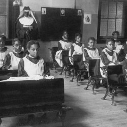 black and white picture of girls school and nun in the back