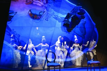 actors on stage dance with the bright blue projection in front of them