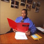 LaMont Toliver in office with folders and papers