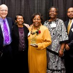 Group of people pose with Legends of Excellence award