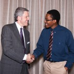 two men shake hands at scholar luncheon