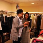 Women stand in room full of professional clothes