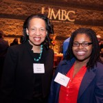 Two women in name tags pose with UMBC sign at Hilltop Society reception