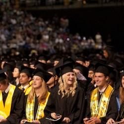 graduating students laugh at undergrad commencement
