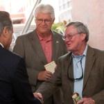 Three men smile and shake hands at Sherman dedication