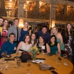 Large group pose around table at wine tasting