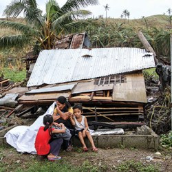 picture of small family and destroyed house after storm