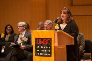woman smiles behind podium at alumni awards