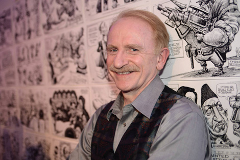 man stands in front of wall full of black and white cartoons