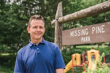 Beller in front of Missing pine park sign
