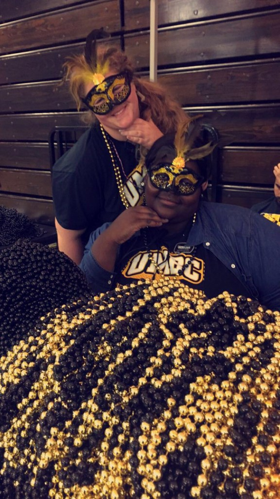 two students in UMBC gear pose with black and gold beads