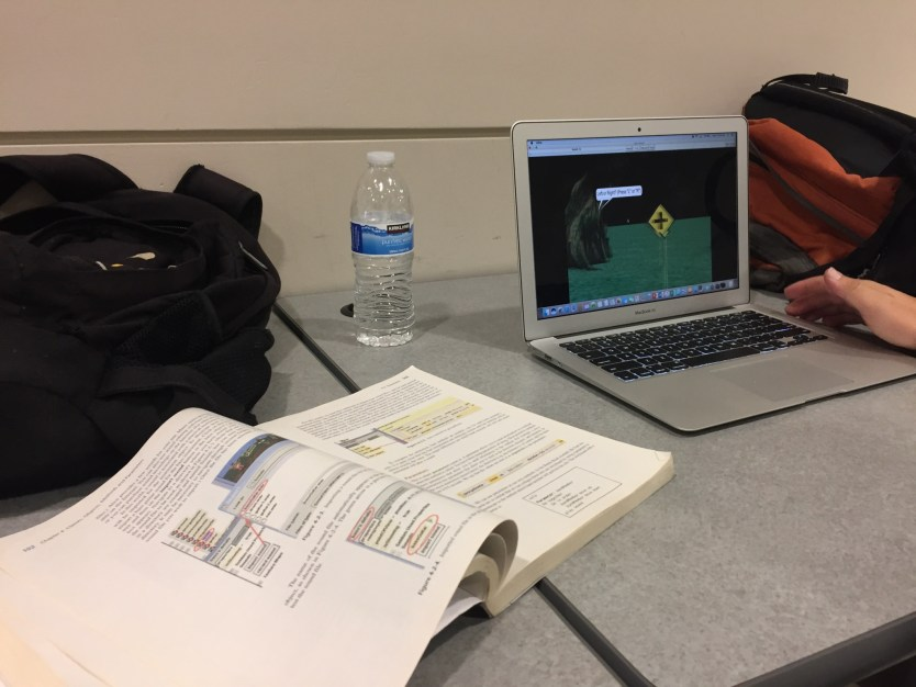 textbook, backpacks and hand on laptop