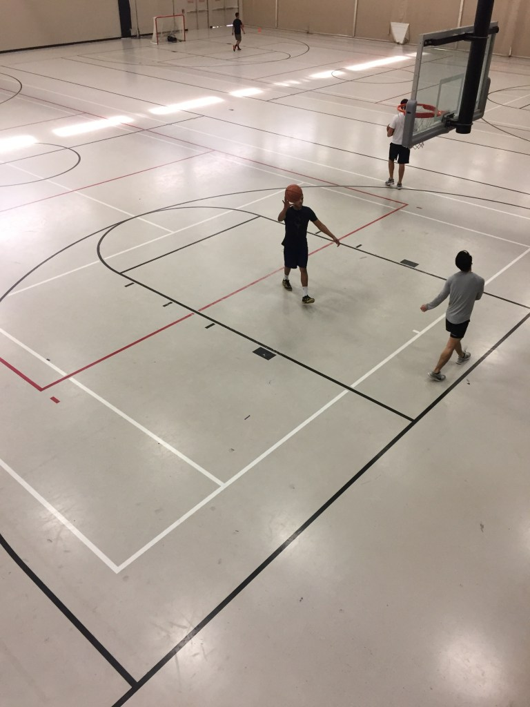 Three people play on basketball court