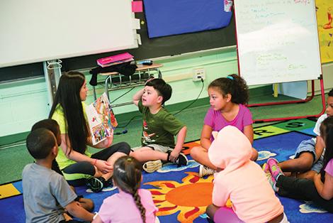 A UMBC STUDENT TEACHER READS TO LAKELAND ELEMENTARY SCHOOL STUDENTS.