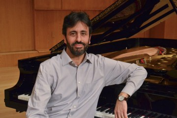 Alejandro Cremaschi poses in front of piano