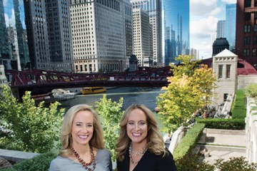 Two women pose with city background