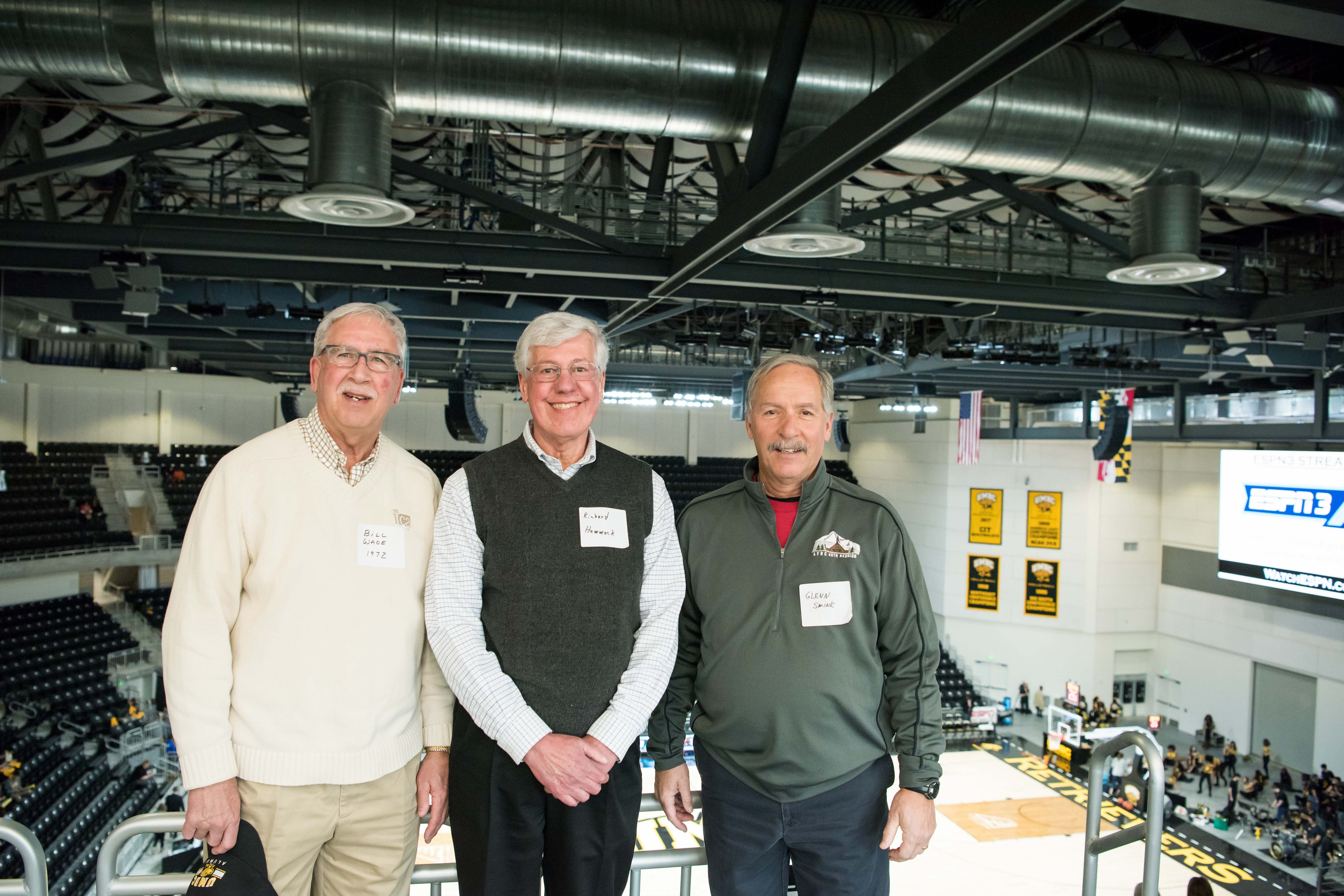 Three men with name tags pose together for event center opening