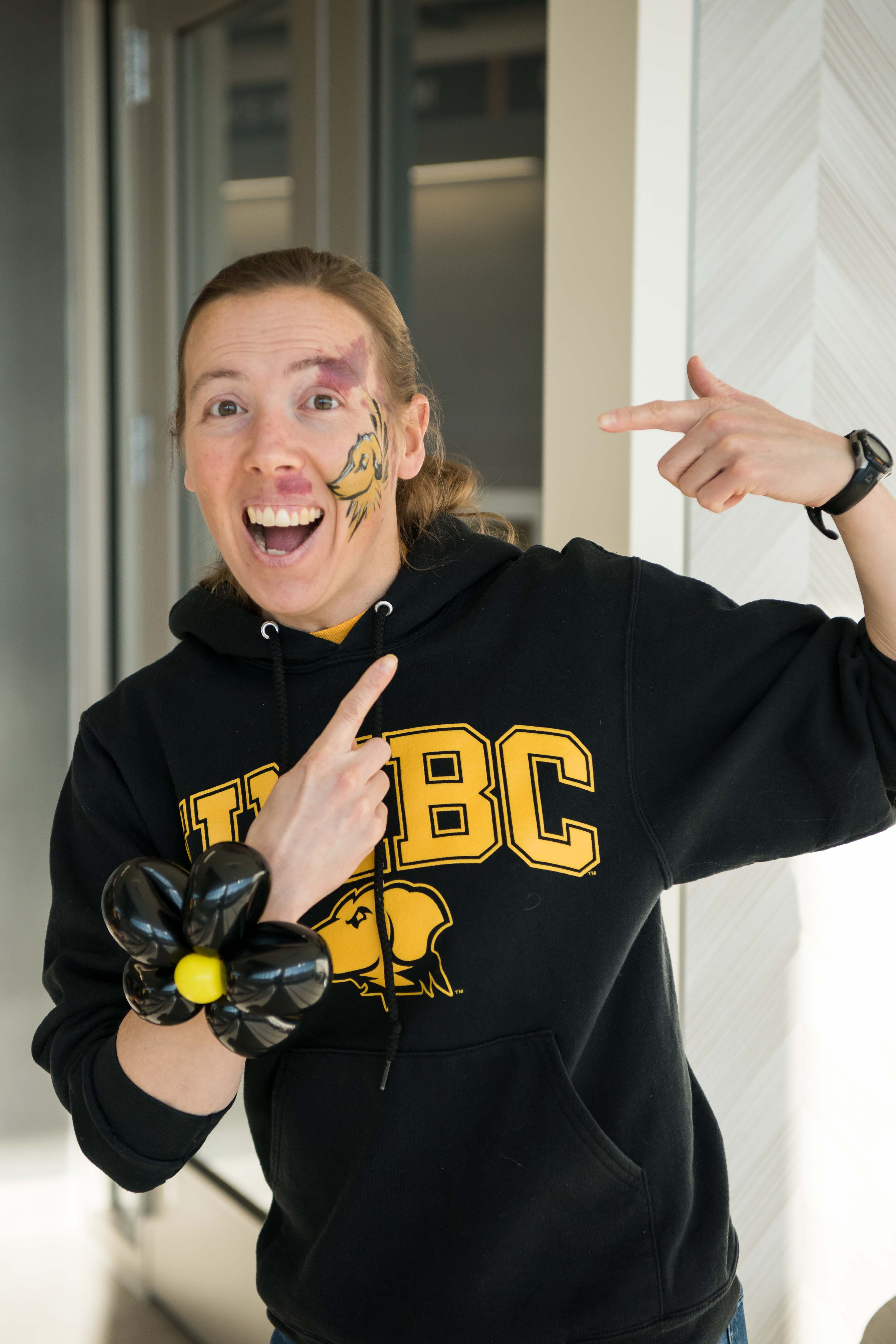 Staff member points to face paint in UMBC hoodie
