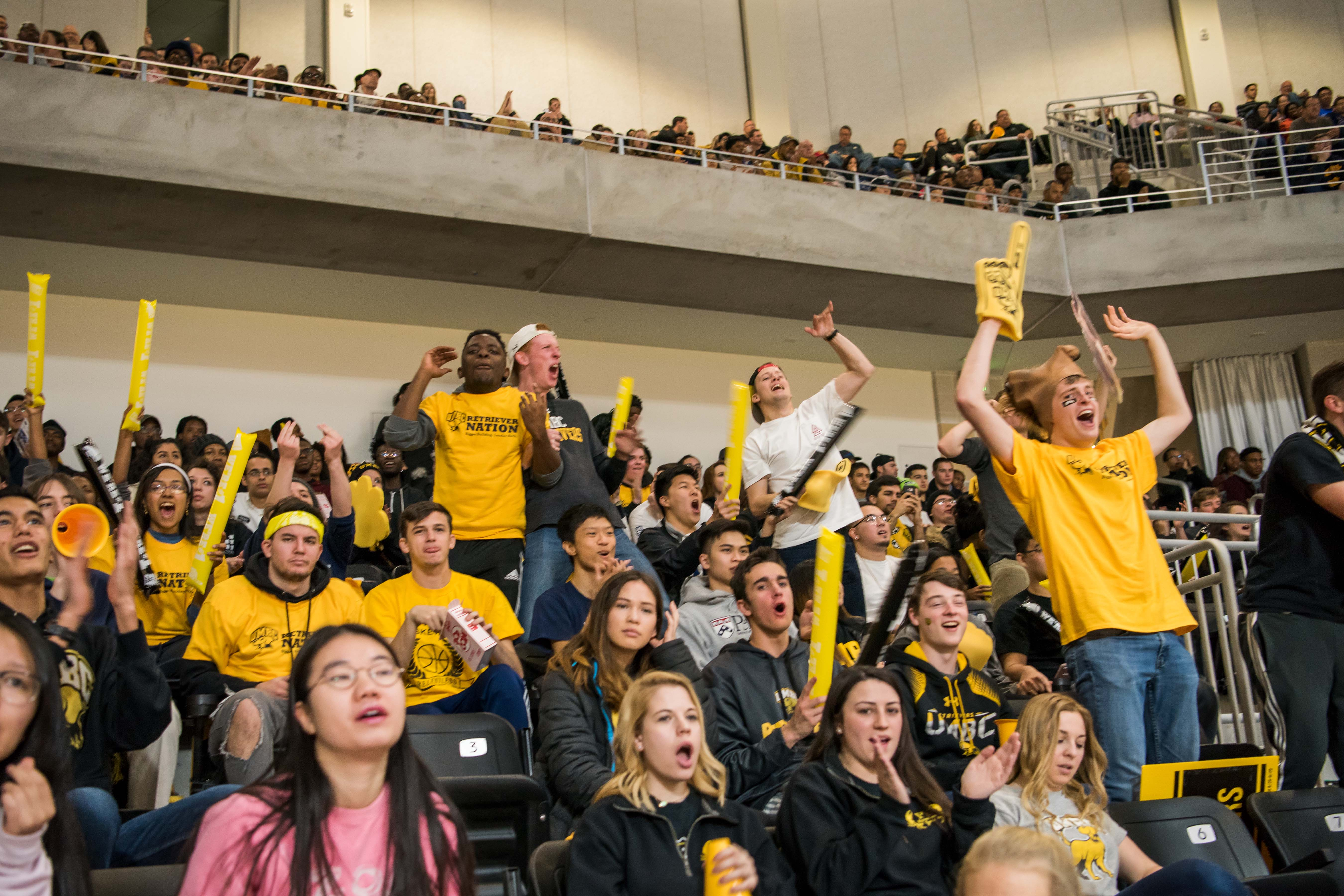 People get up and cheer crowd filled with UMBC gear at basketball game