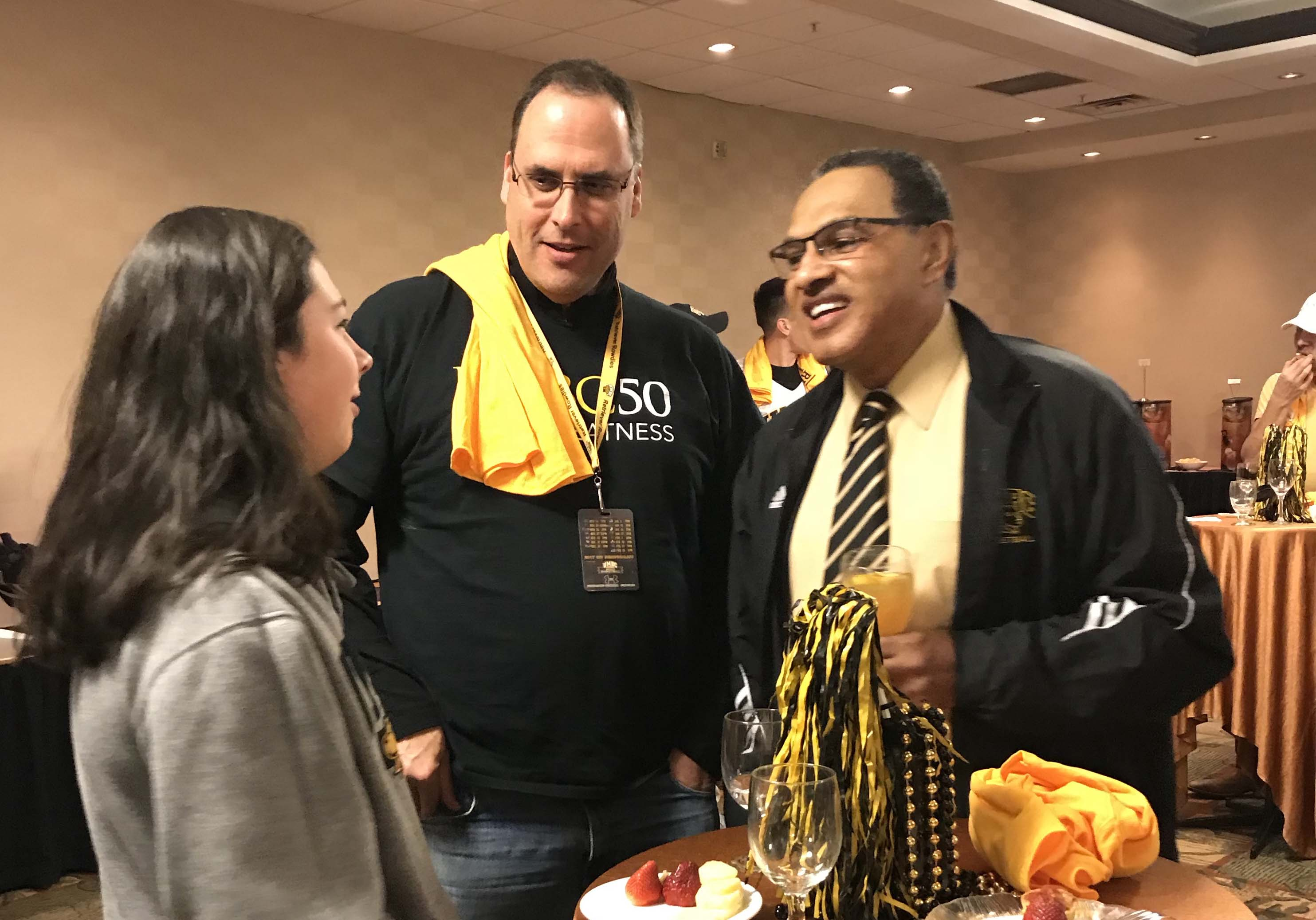 Hrabowski talks with others around round tables with UMBC gear