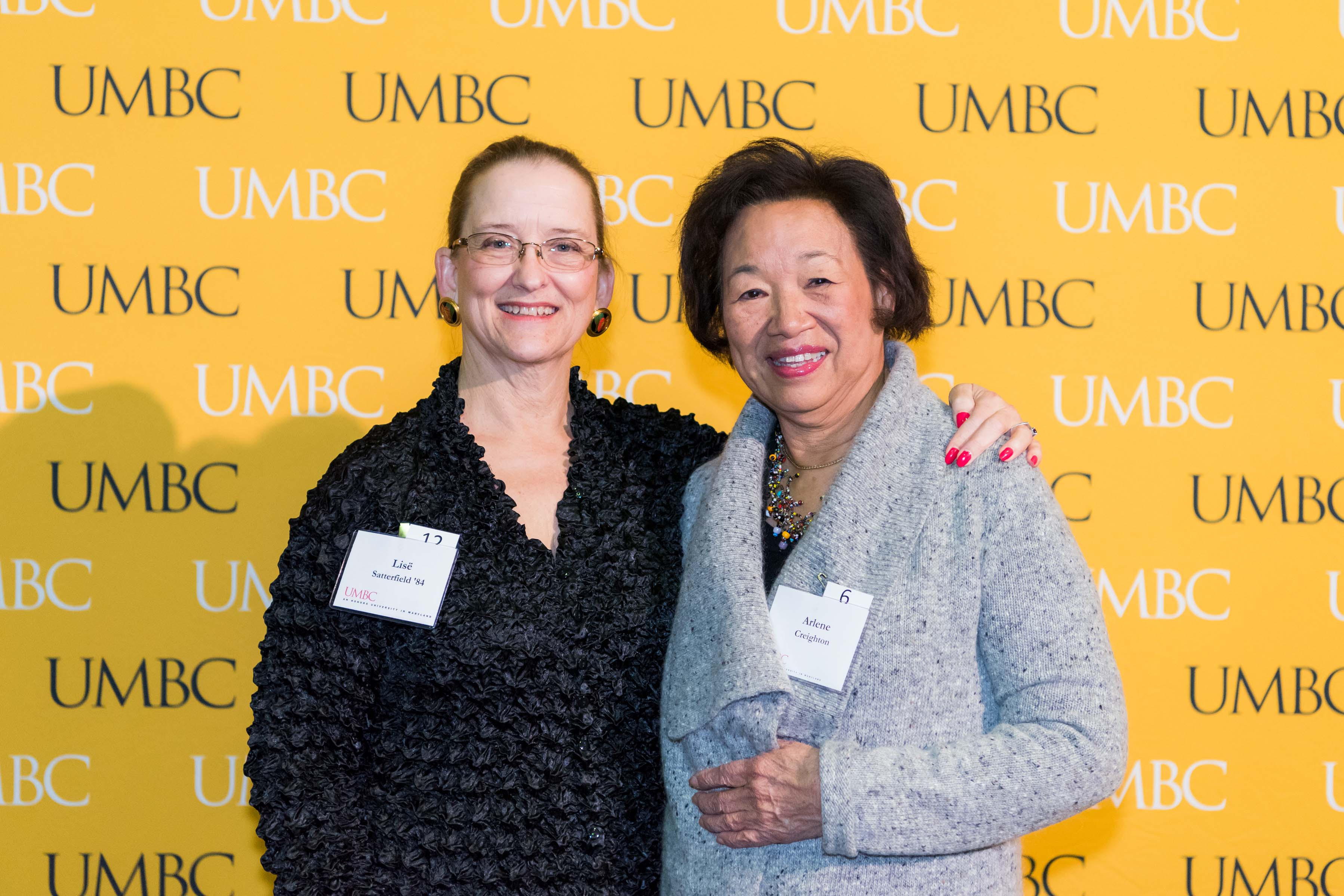 Two women pose in front of the UMBC wall at the scholarship luncheon