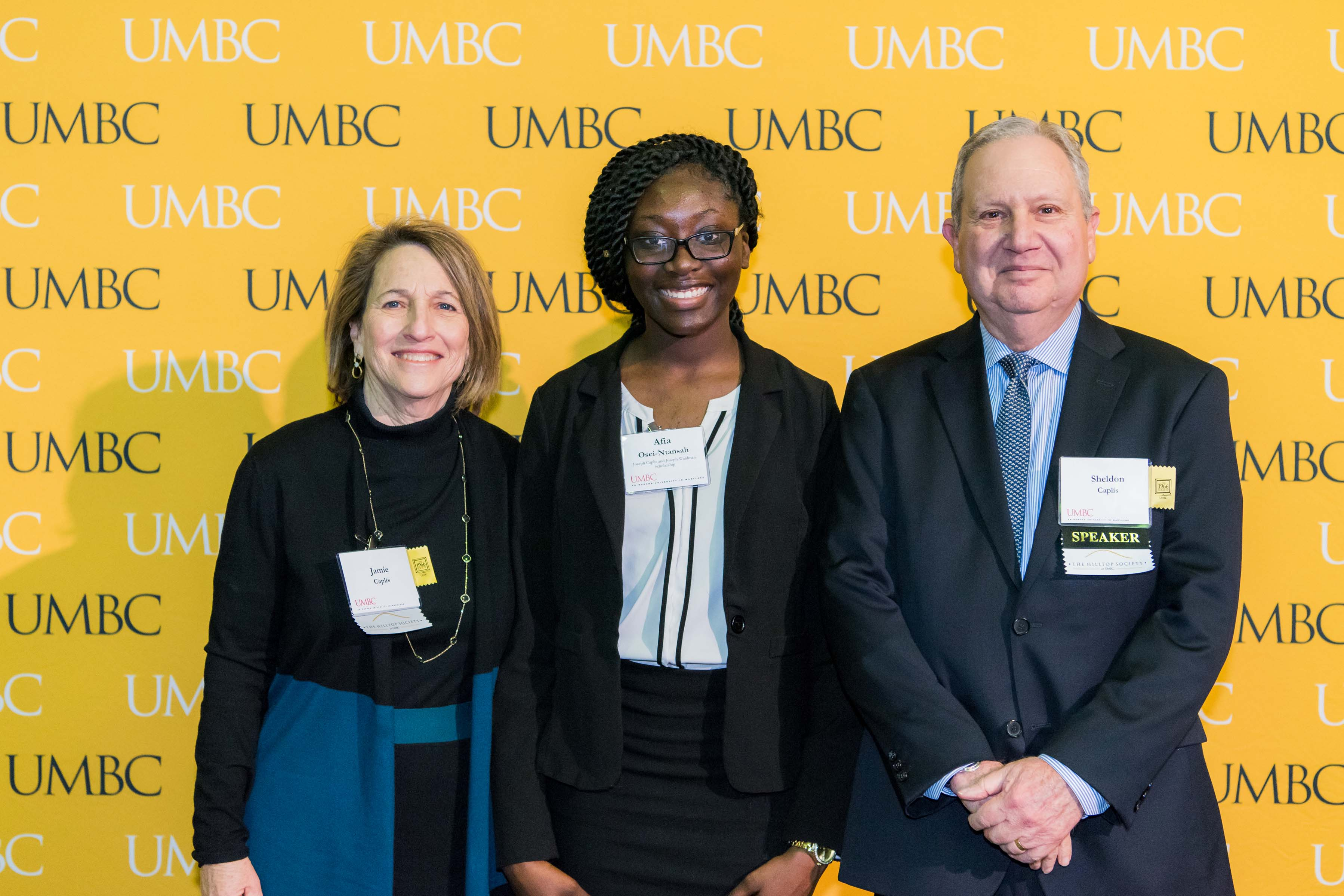 Group of three pose in front of the UMBC wall at the scholarship luncheon