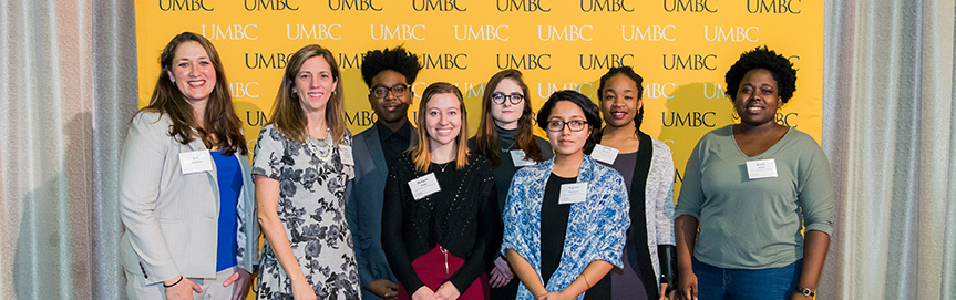 Large group pose in front of the UMBC wall at the scholarship luncheon