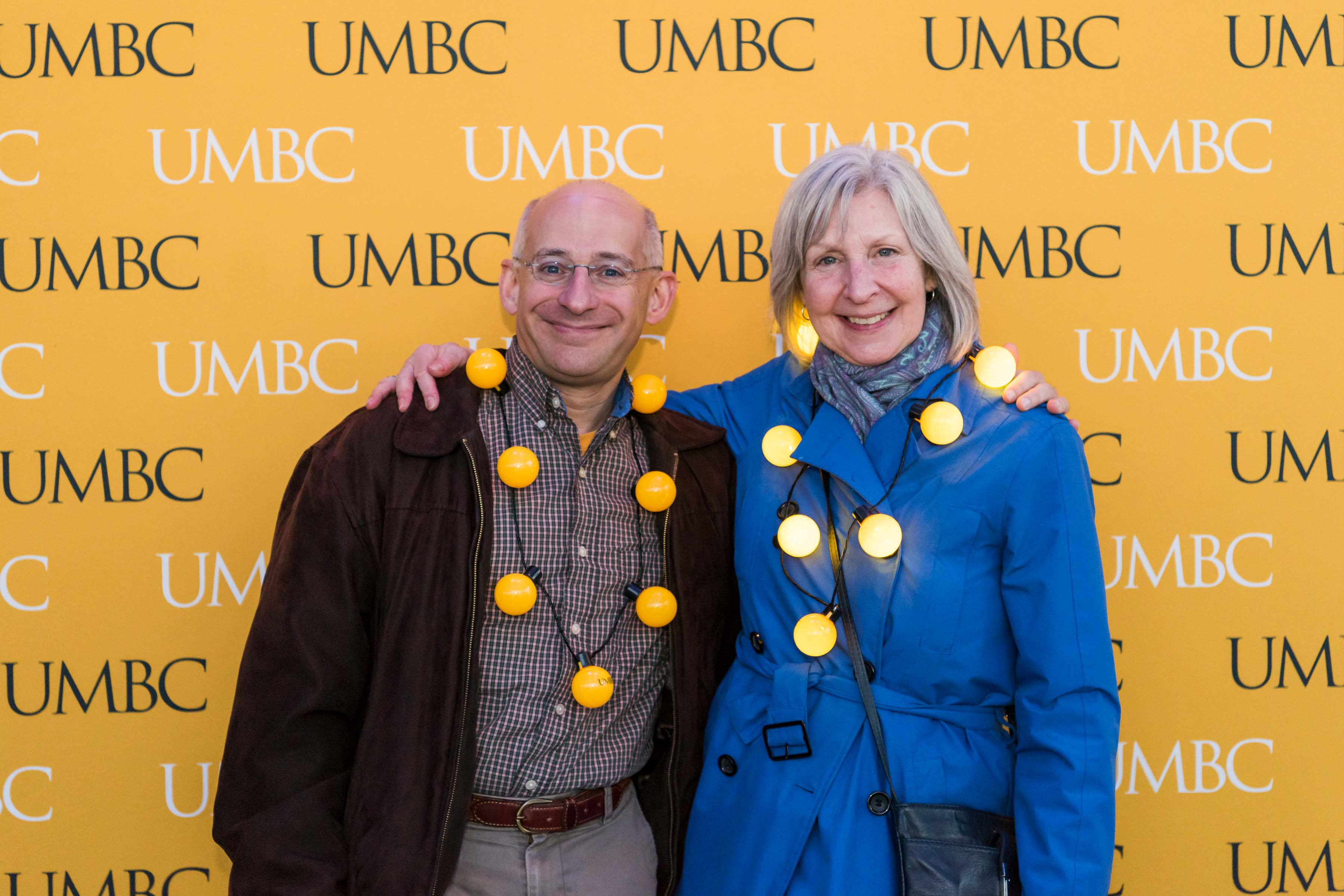Couple poses in front of UMBC wall at alumni reception