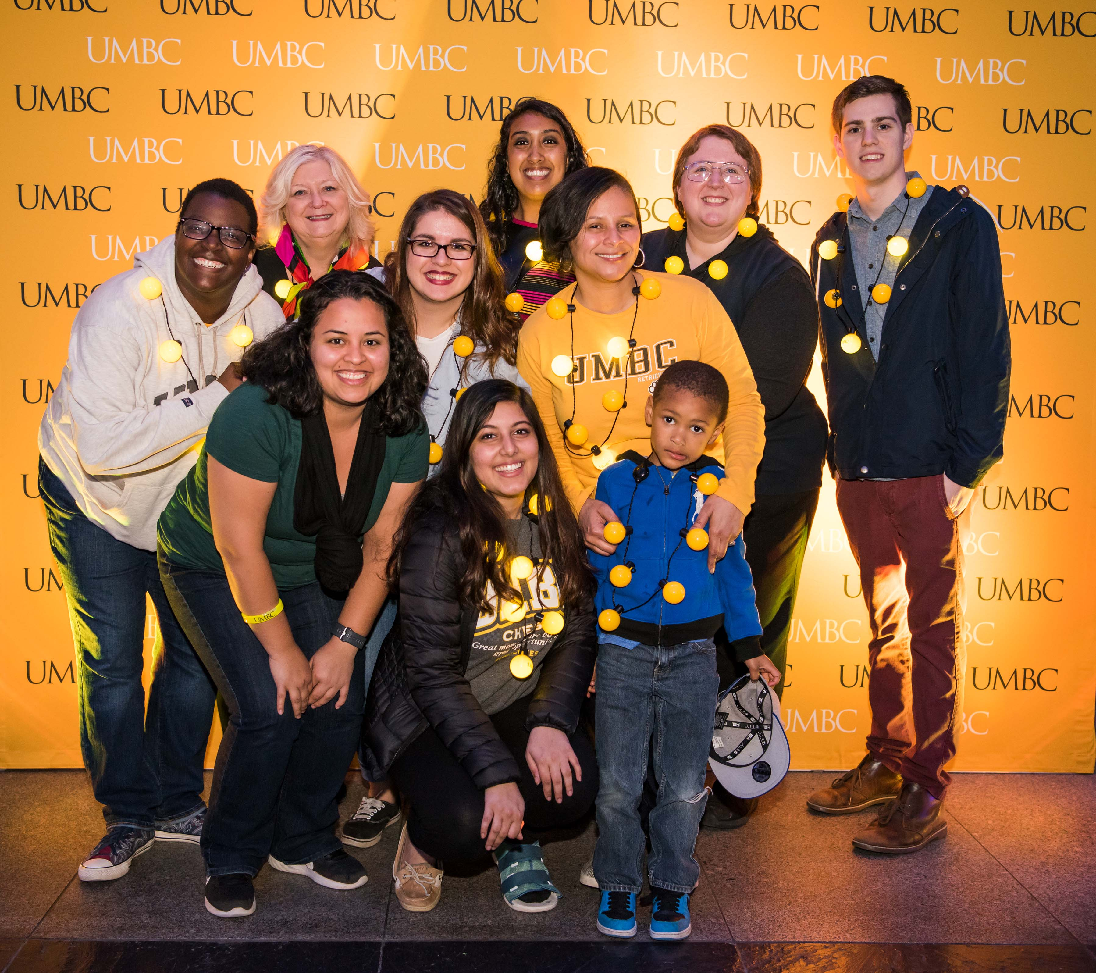 Large group pose in front of UMBC wall at alumni reception
