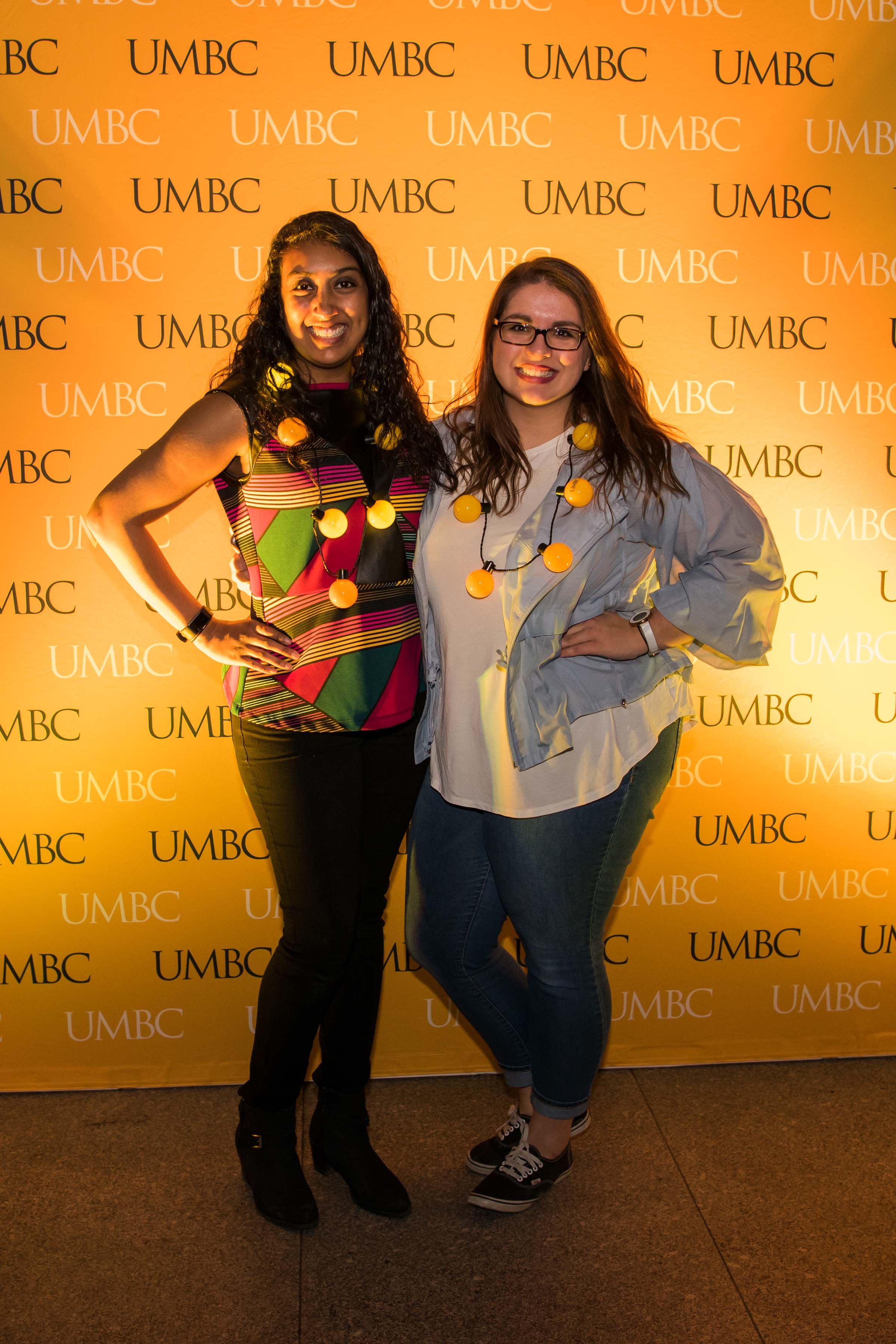 Two women with their lightbulb necklaces pose in front of UMBC wall at alumni reception