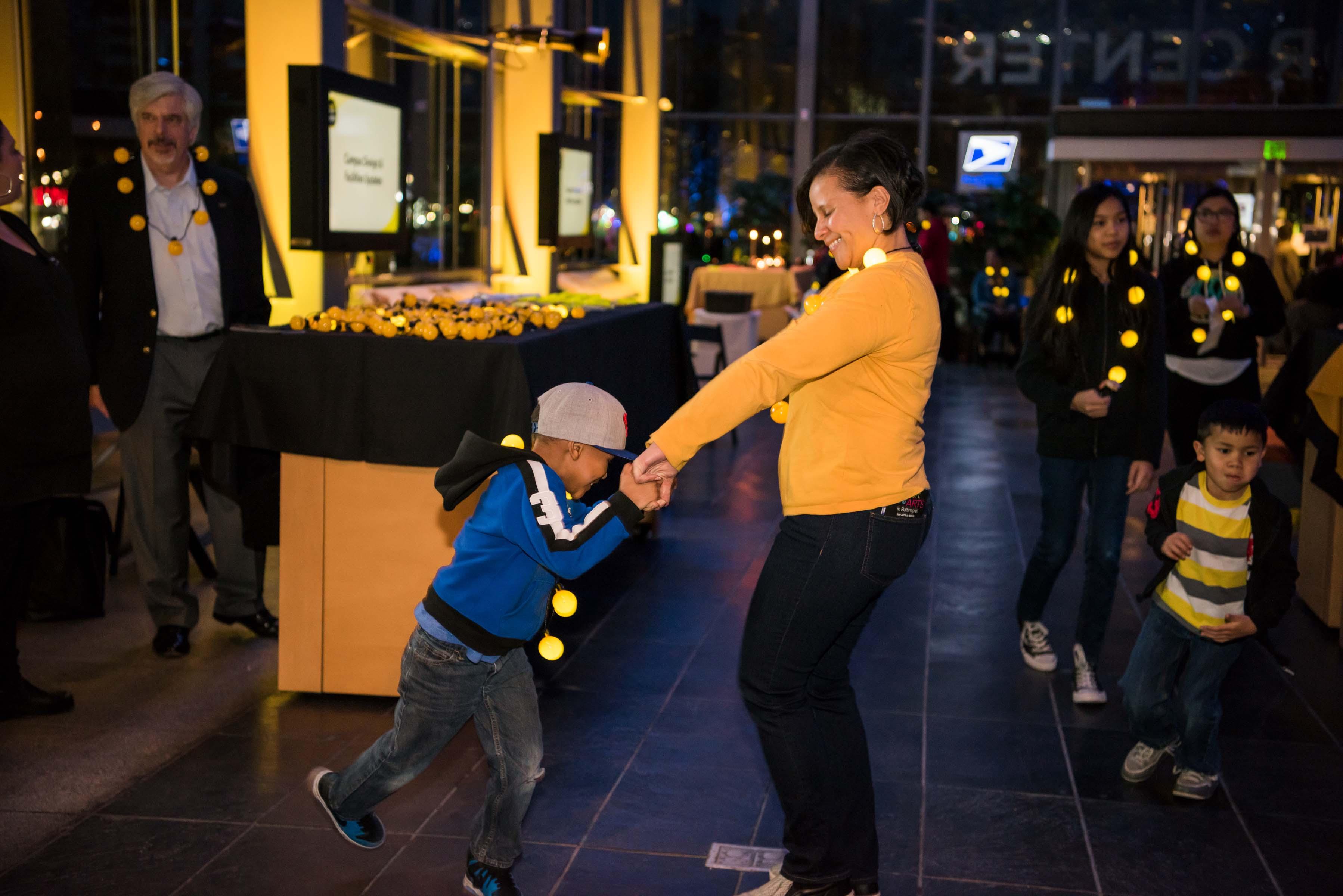 Women dances with little boy at alumni reception