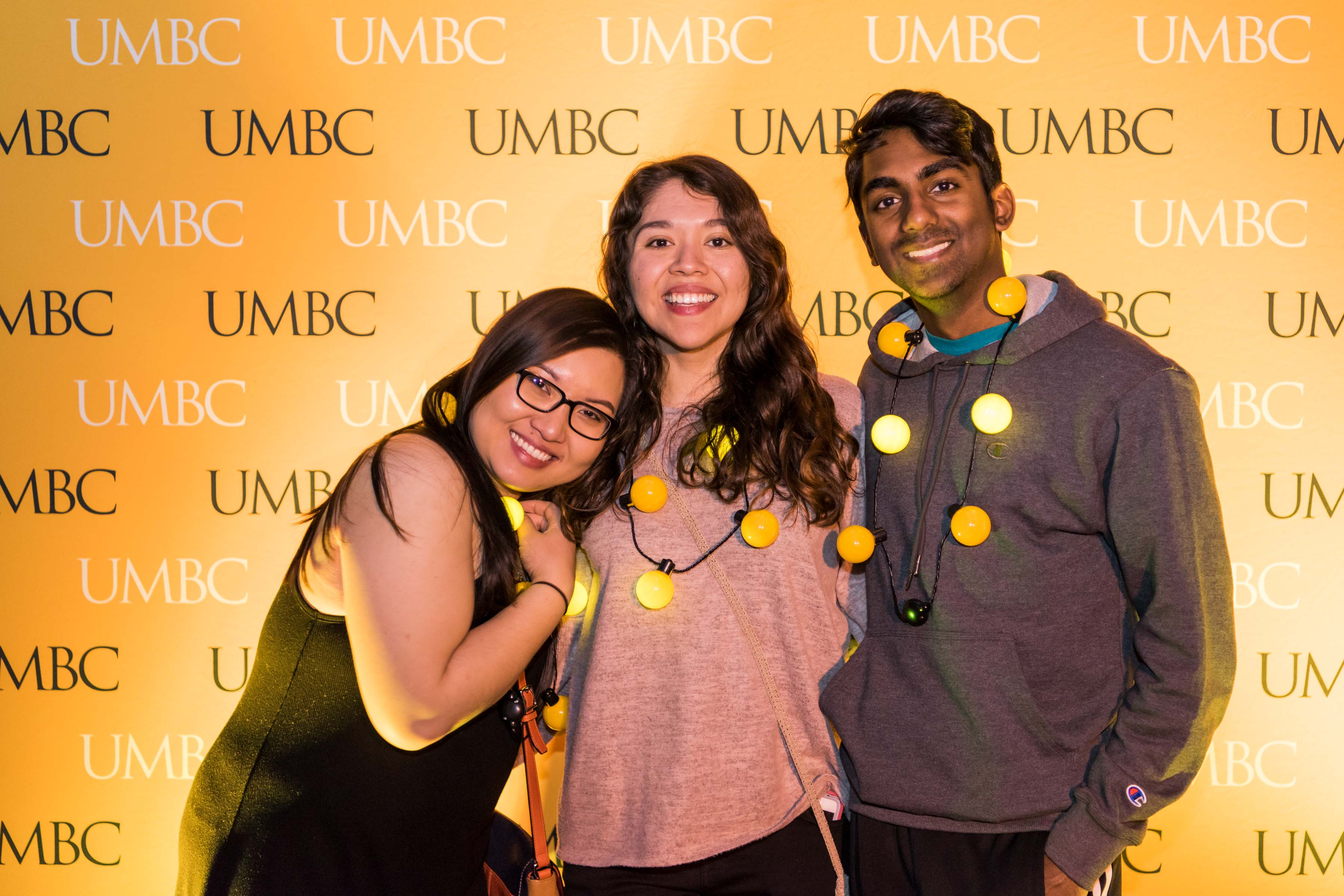 Group of friends pose in front of UMBC wall at Pier 5 reception