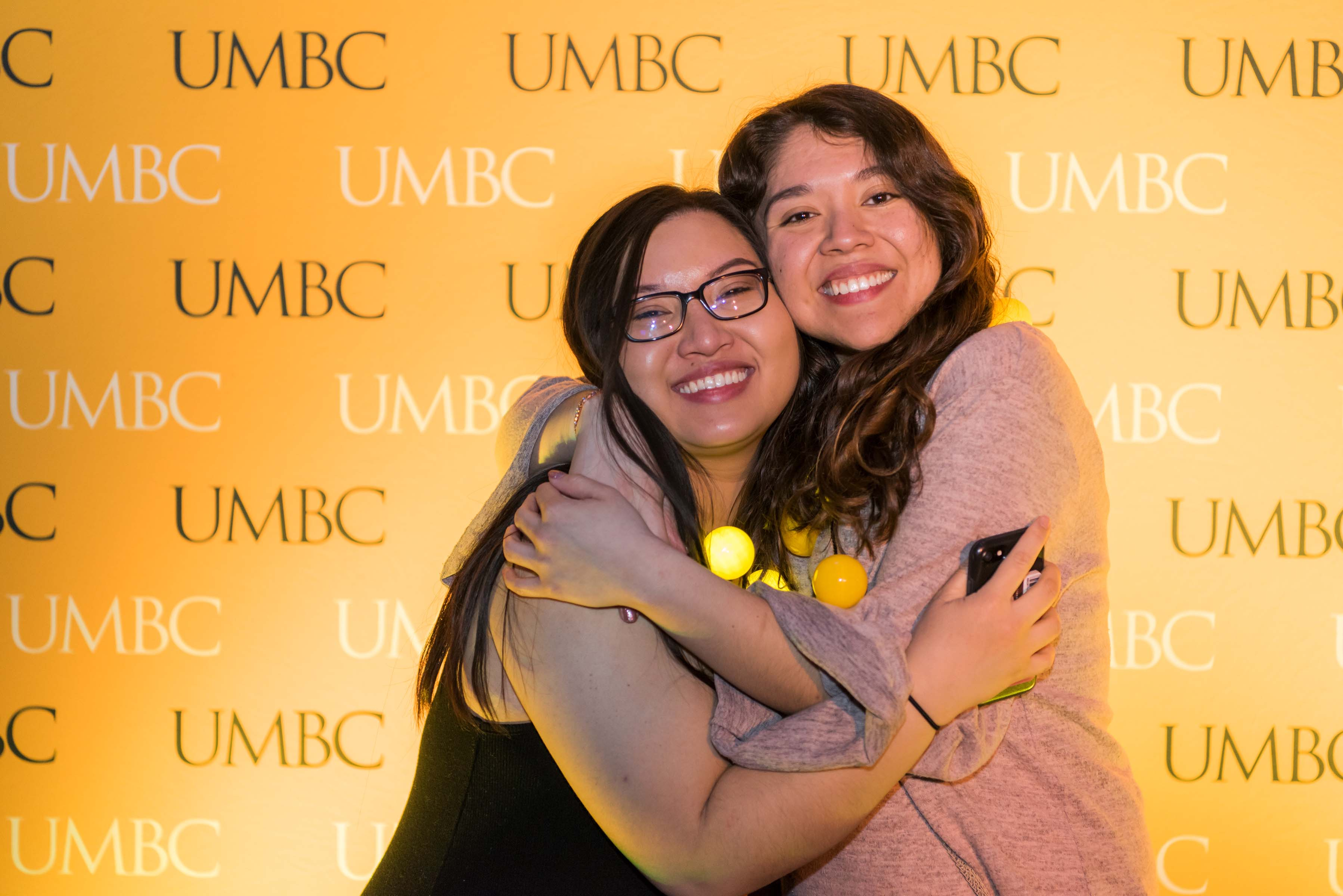 Two girls embrace in front of UMBC wall at Pier 5 reception