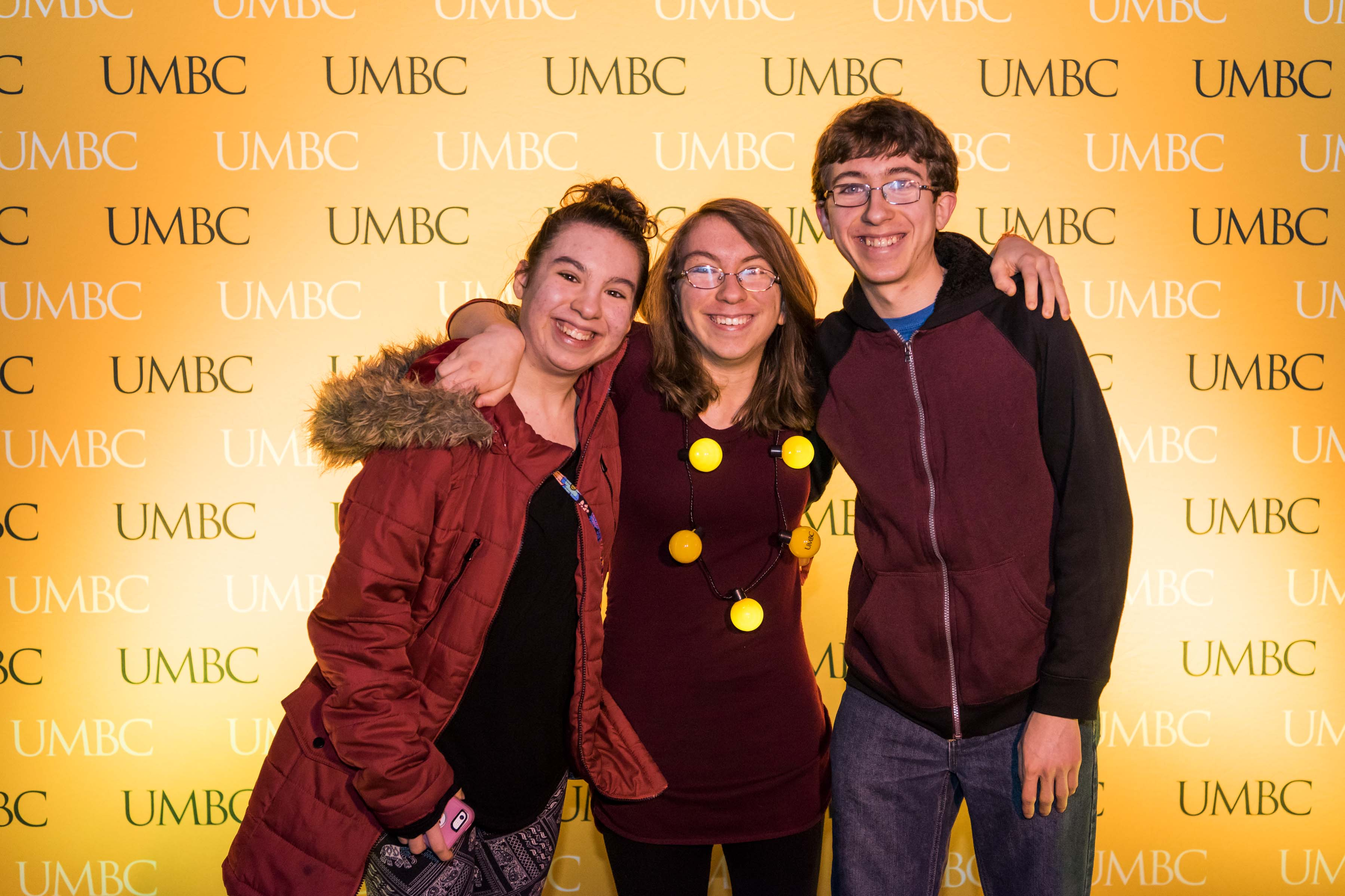 Siblings pose in front of UMBC wall at Pier 5 reception