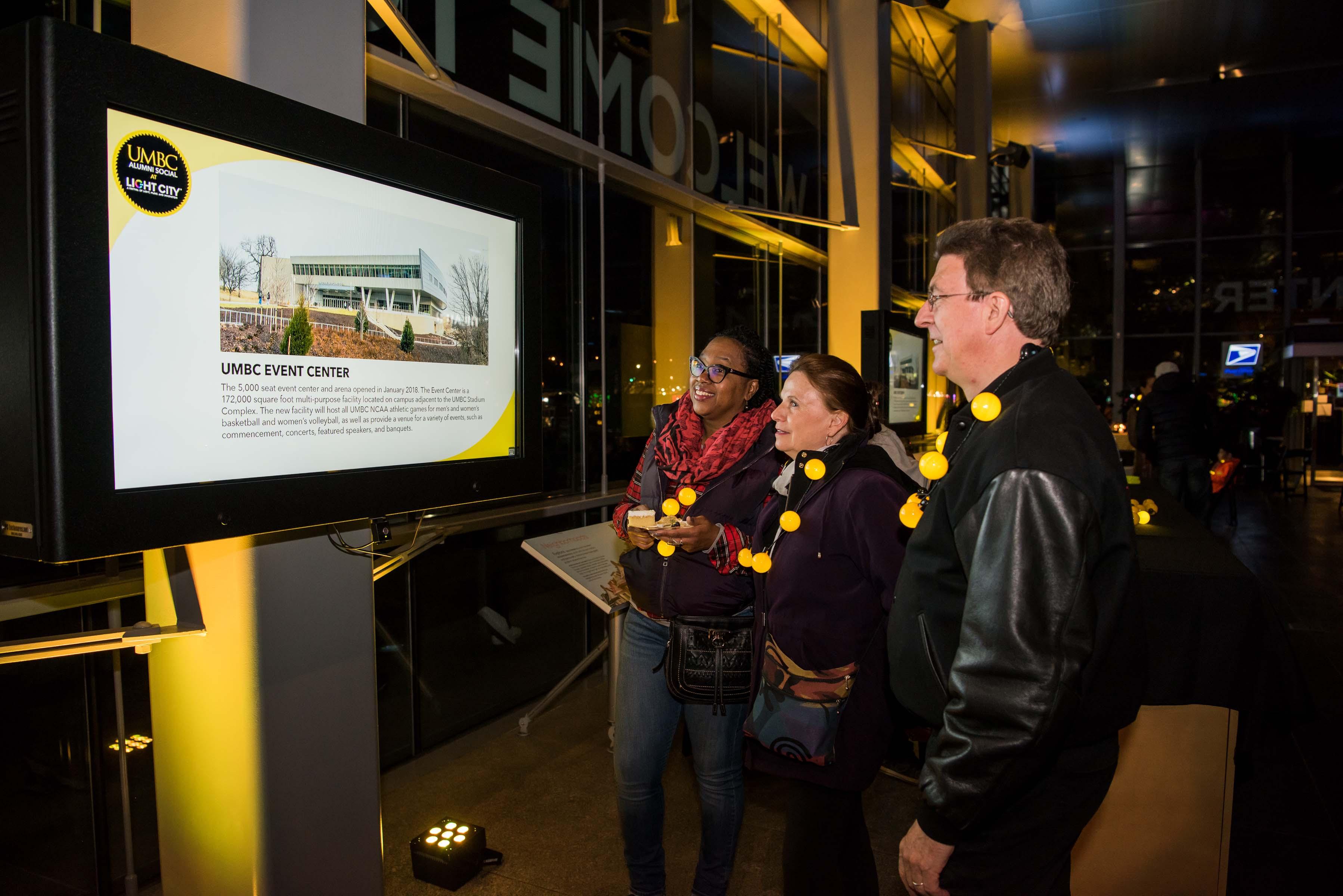 Group looks at UMBC event center slide on screen