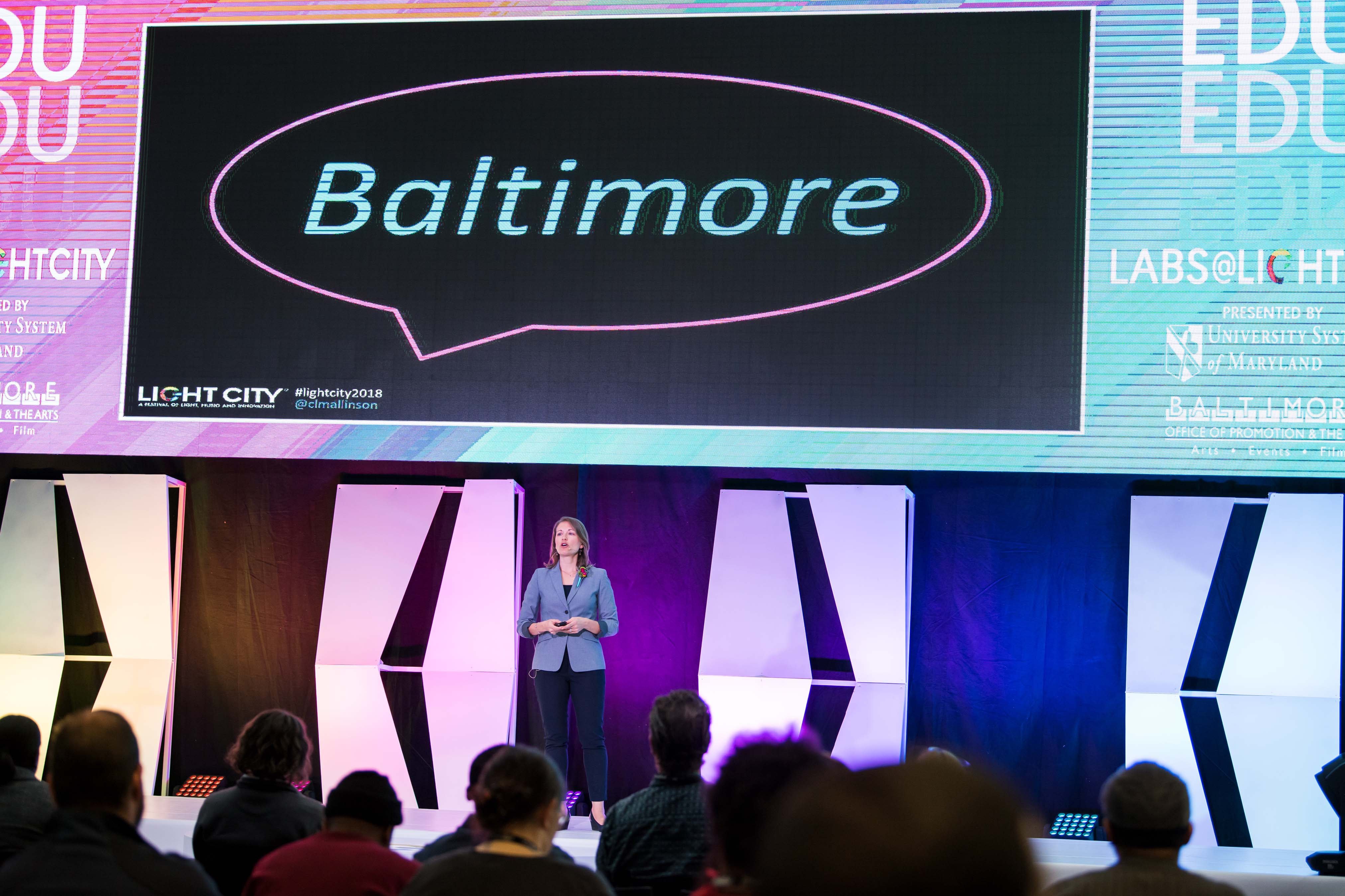 Woman stands on stage Baltimore on huge screen behind her
