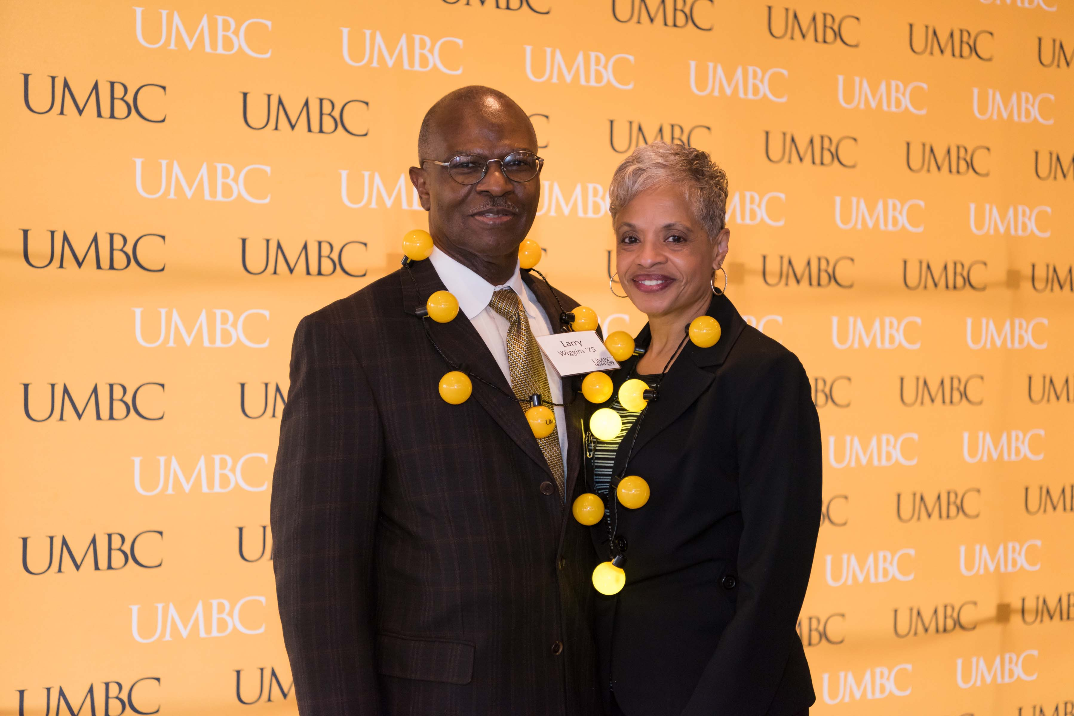 Couple pose in front of UMBC wall at Pier 5 reception