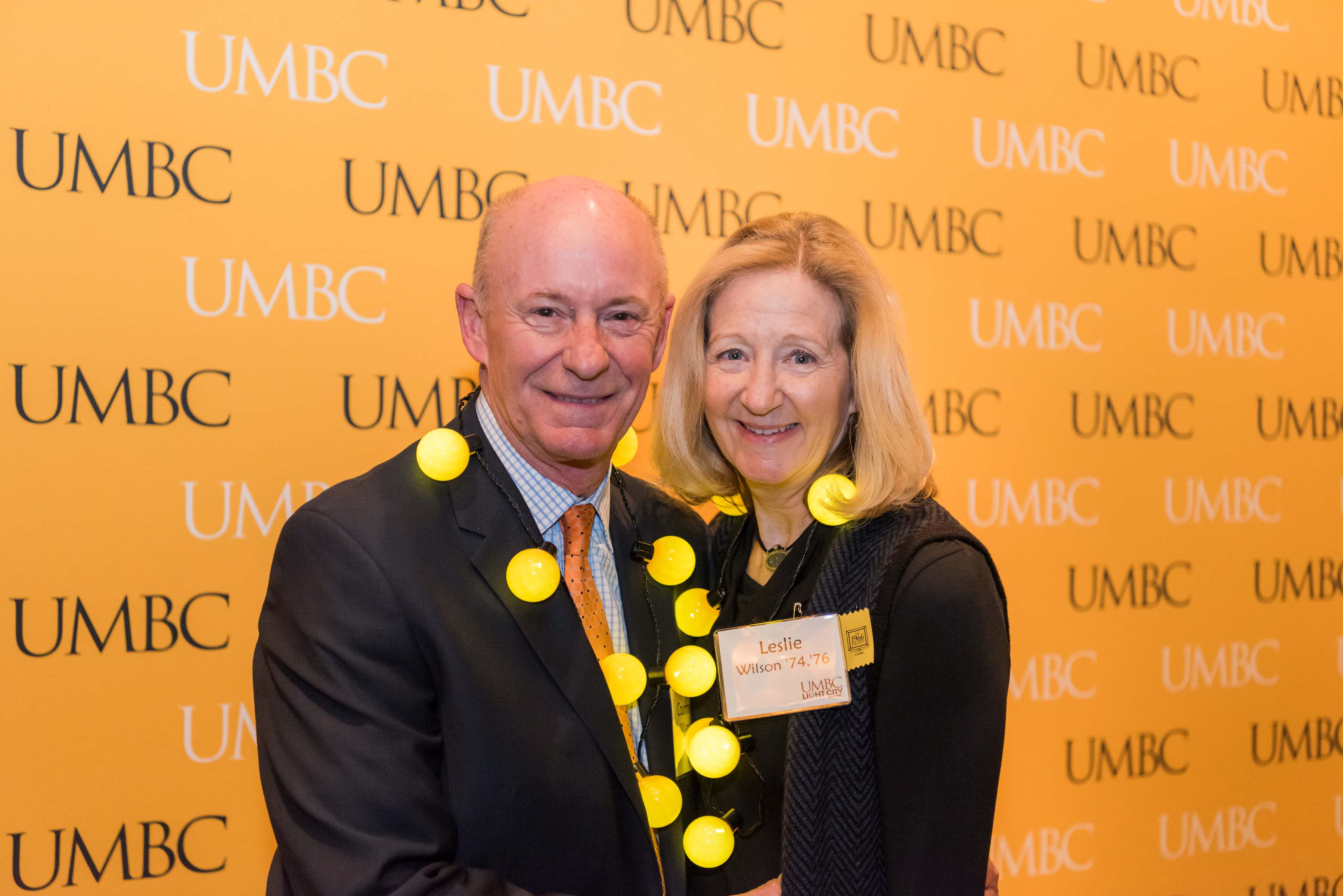 Leslie Wilson poses with man in front of UMBC wall