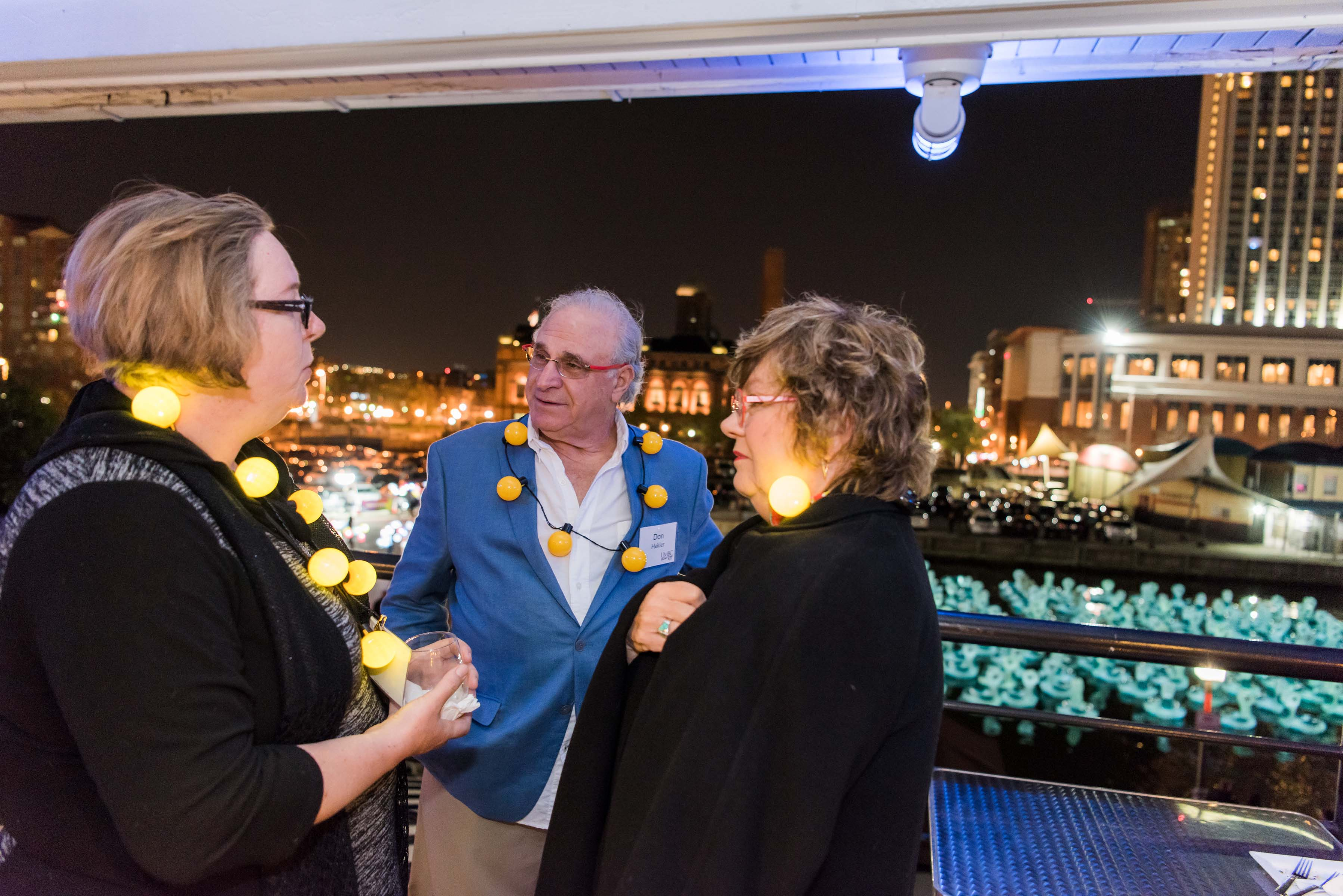 People with bulbs around their necks talk at Light city reception