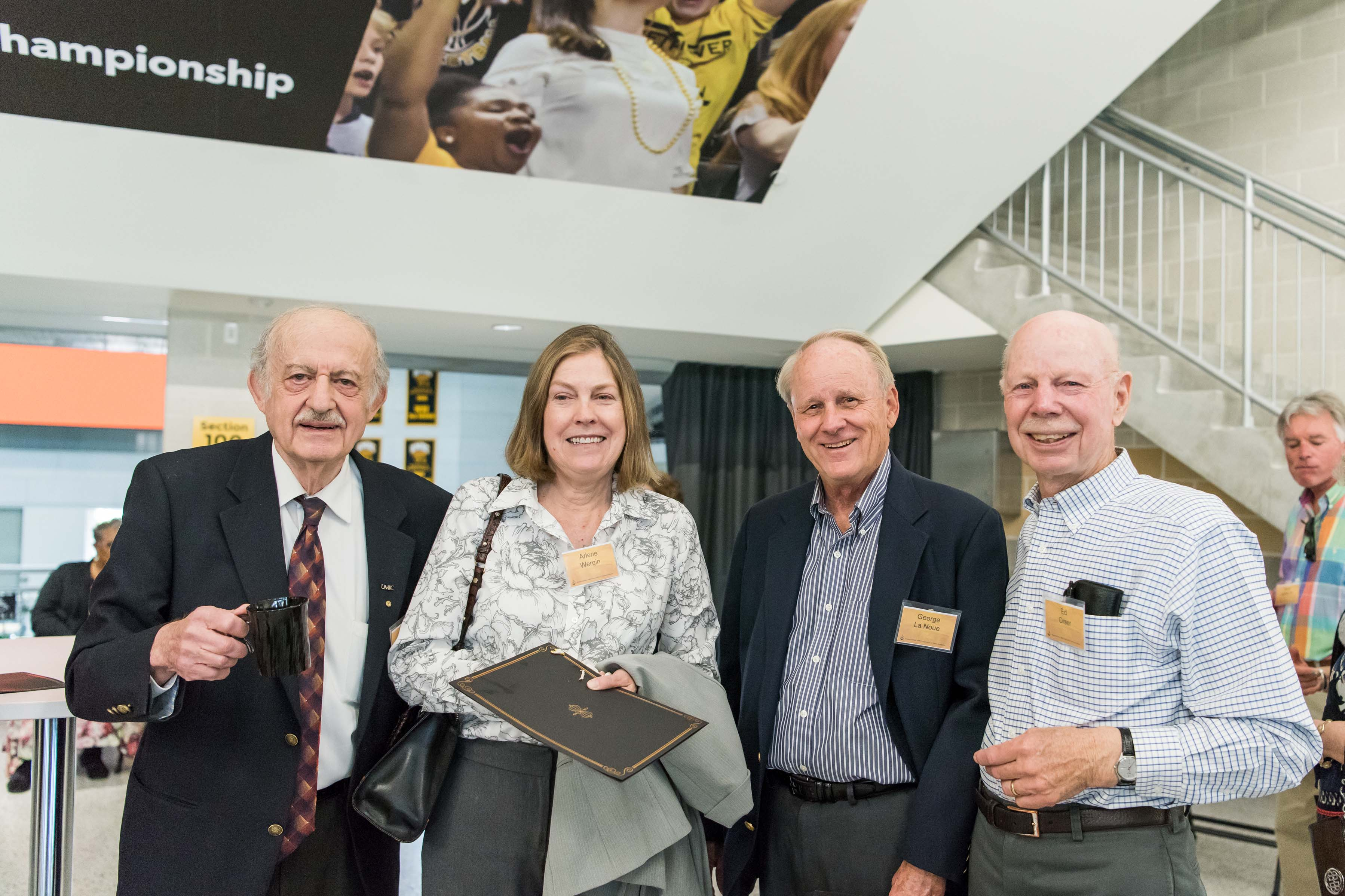 Group of four pose together at Wisdom Institute lunch
